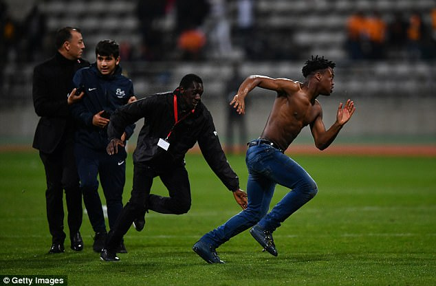 Stewards attempts to catch a topless pitch invader after the players had exited the field of play