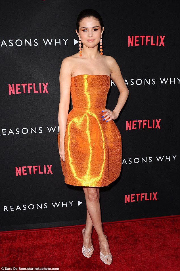 Golden girl: Selena Gomez was unmissable in tangerine as she stepped out on the red carpet for the premiere of 13 Reasons Why in Los Angeles on Thursday