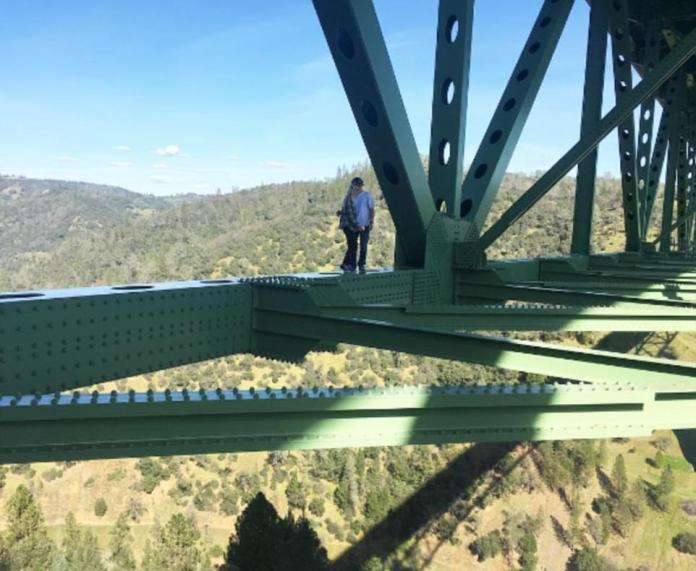 One wince-inducing photo shows a reckless couple embracing on a ledge after weaving their way across the precariousgirders