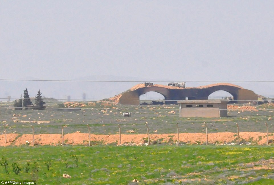 On the ground: These damaged hangars, blackened by smoke, are at the entrance to the Syrian airfield bombarded by the US. The US targeted several such shelters across the military base, which it said held chemical weapons