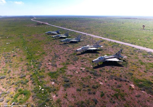 Unscathed: This collection of five jets on al-Sharyat Air Base somehow escaped the bombing raid, despite being located out in the open, on a patchy grass plain