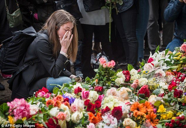 Minute's silence: In front of a sea of flowers, a woman weeps with emotion as Sweden fell silent for a minute's commemoration for the victims of Friday's terror attack