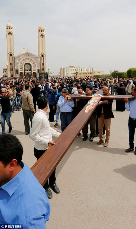 Men carry a cross as mourners gather for the funeral of the victims of the Palm Sunday bombings at the Monastery of Saint Mina