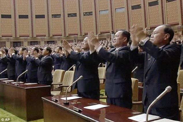 Officials stand and applaud as Kim Jong Un presides over the parliament meeting on Tuesday