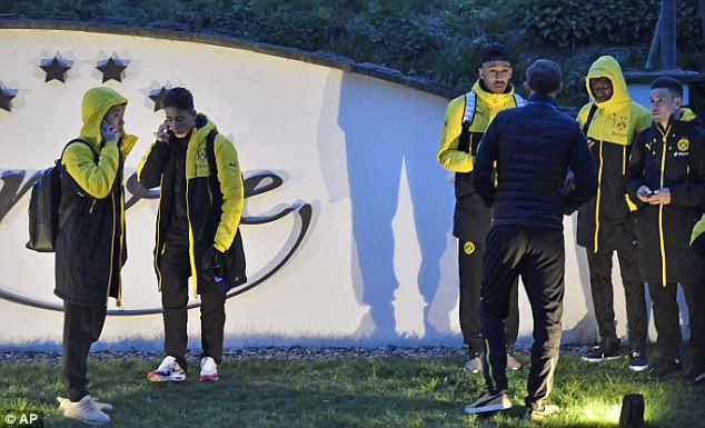 Dortmund players stand outside the team bus after it was damaged in an explosion on Tuesday night in western Germany
