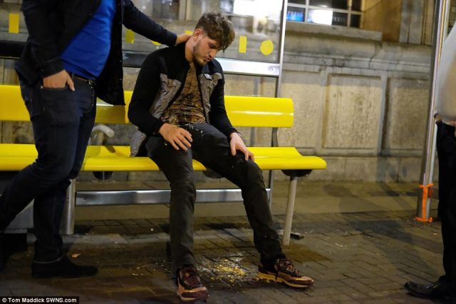 Others looked worse for wear, including this man who was slumped up against a bench in Liverpool after appearing to be sick, with concerned friends tending to his welfare
