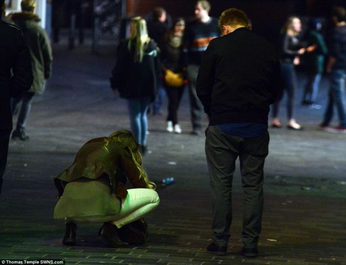 One was woman was pictured crouched down in the middle of the street in Liverpool city centre as a man, appearing to rummage through her bag