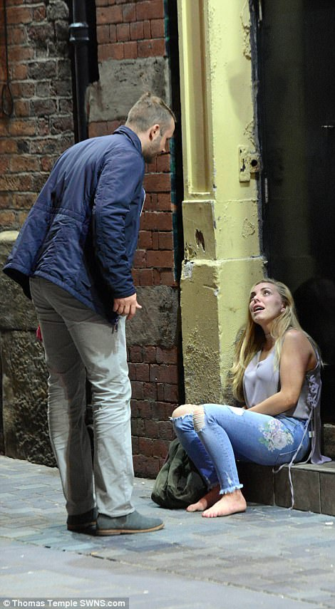 A man and woman are pictured locked in conversation as she sits in a doorway in Liverpool