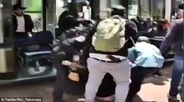 Video from the scene shows police and members of the public dragging the man from the tram by his arms and legs before he is arrested