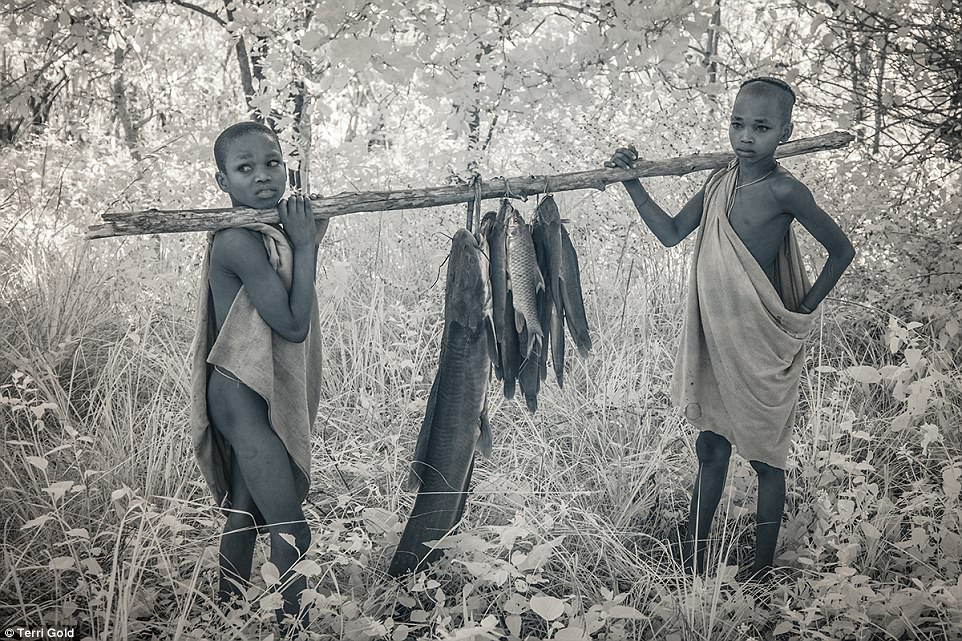 Young Suri boys in Ethiopia bring home freshly caught fish