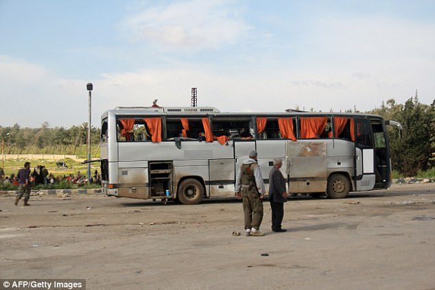 Rebel fighters stand next to a damaged bus following the suicide car bombing