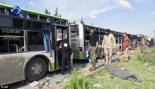 Rebel gunmen stand at the site of a blast that damaged several buses carrying evacuees