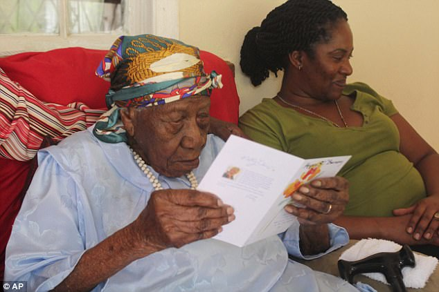 Violet reads a card on April 16 at hre home in Duanevale, Jamaica