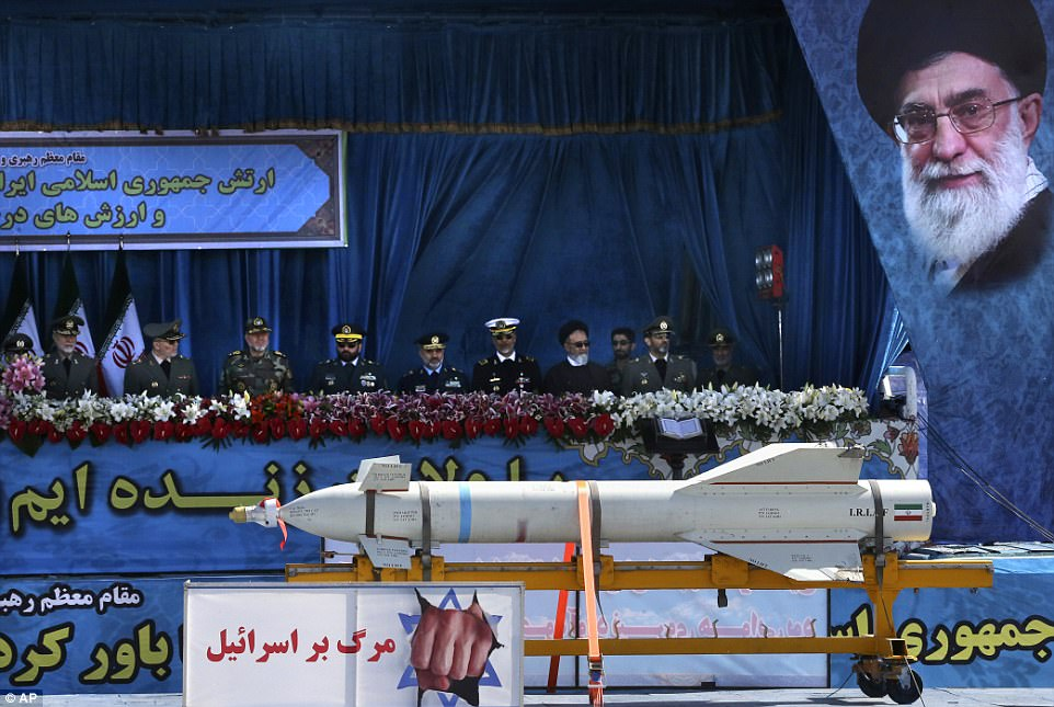 A missile with an anti-Israeli banner, which reads in Persian, 'Death to Israel,' is displayed, as Iranian armed forces commanders review an army parade next to a portrait of Supreme Leader Ayatollah Ali Khamenei on National Army Day, in front of mausoleum of the late revolutionary founder Ayatollah Khomeini, just outside Tehran, Iran