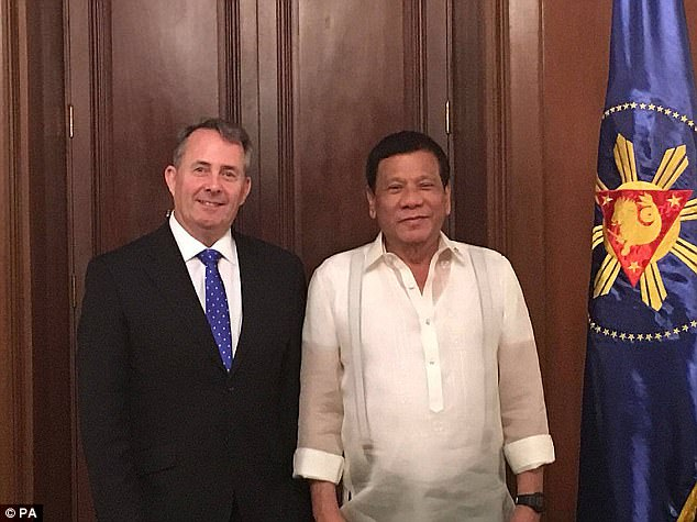 It also claims that civilian members of the so-called Davao Death Squad, which rights activists allege killed hundreds of people in Duterte's hometown of Davao, were drafted to 'augment and assist' the police's current nationwide anti-drug operation. Pictured, Duterte withTrade Secretary Liam Fox)