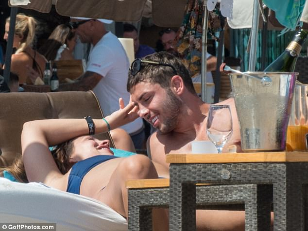 This is the life: Additional photos show the two walking arm in arm and cuddled up on a sun lounger together