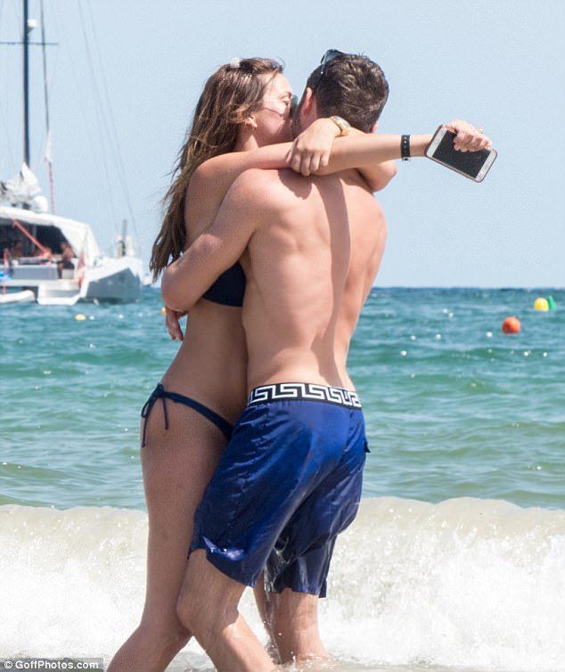PDA: A happy, bikini-clad Ferne, 26, was pictured with her arms around her boyfriend's neck as they kissed on the beach