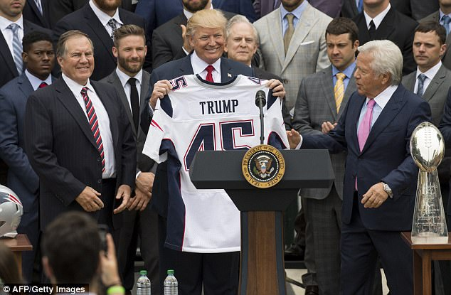 President Trump (center) stands alongside Patriots coach Bill Belichick (left) and Patriots owner Robert Kraft (right), with the players at his back