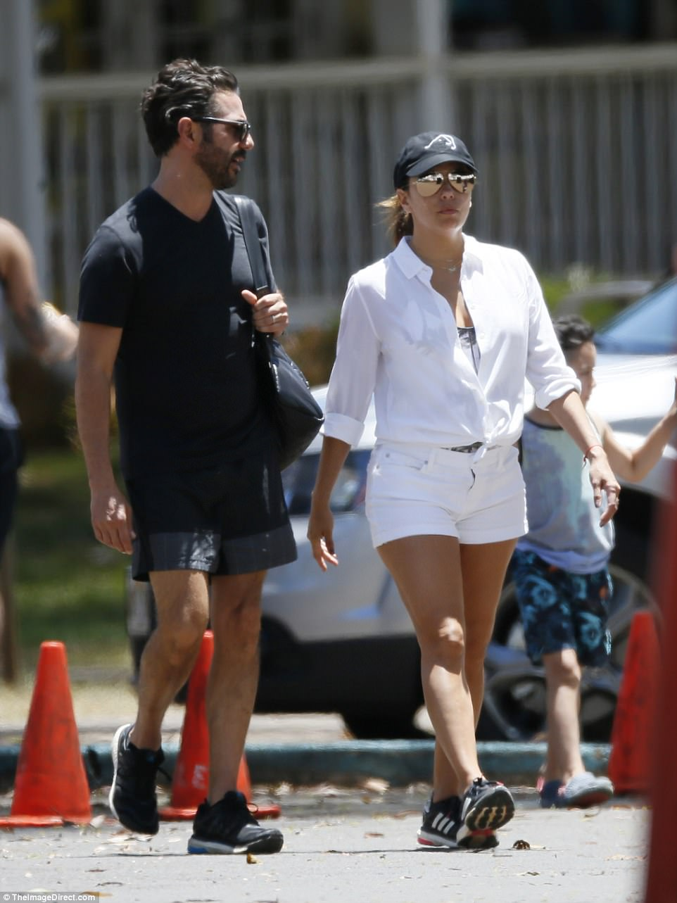 Sporty style: Eva kept cool in a baseball cap and slipped on shorts and some comfy trainers for the walk back from the beach
