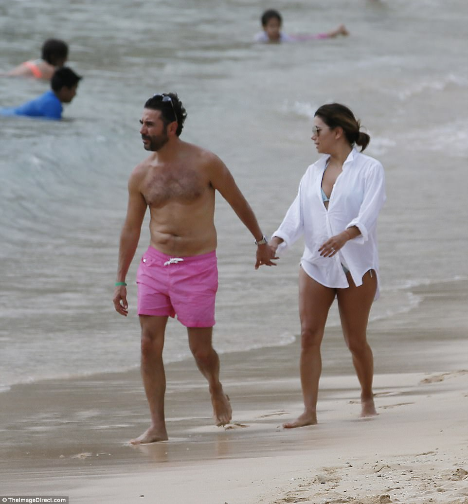 Back on dry land: After her adrenaline rush it was time for a more relaxing stroll along the beach, with Jose rocking a pair of bright pink swimshorts, while Eva slipped on a loose white shirt