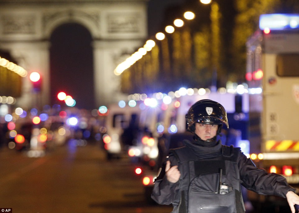 A French police officer stood guard on the Champs Elysees in central Paris following the fatal shooting, which has been described as 'terrorist related'