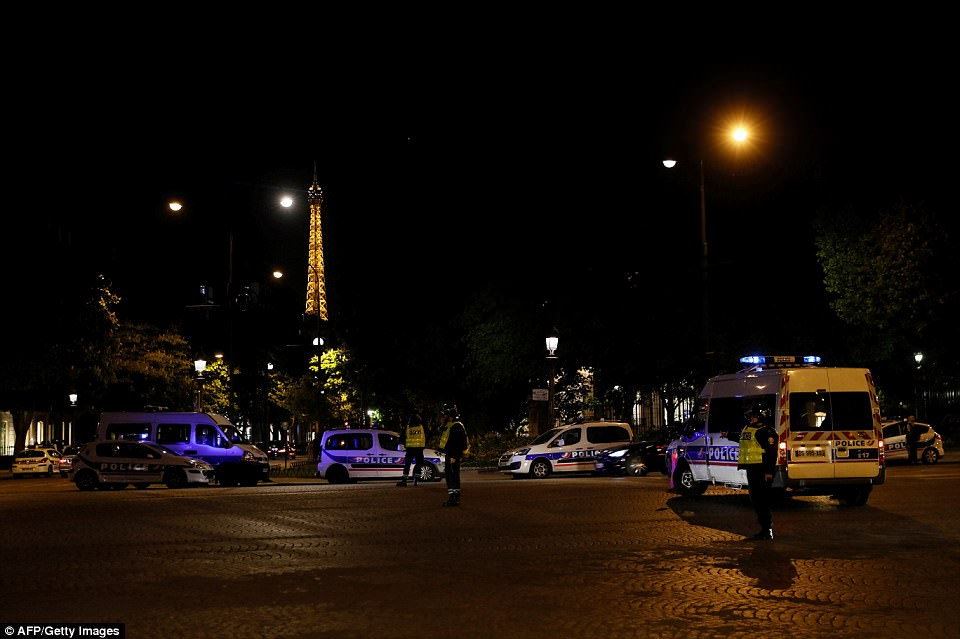 The world famous street was put on lockdown by 9pm and officers guarded the area in central Paris (pictured, the Eiffel Tower in the background)