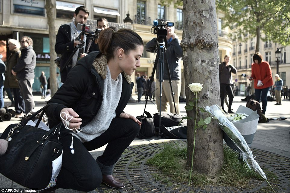 A woman places a flower near the spot on the Champs Elysees where the shooting occurred last night in the French capital