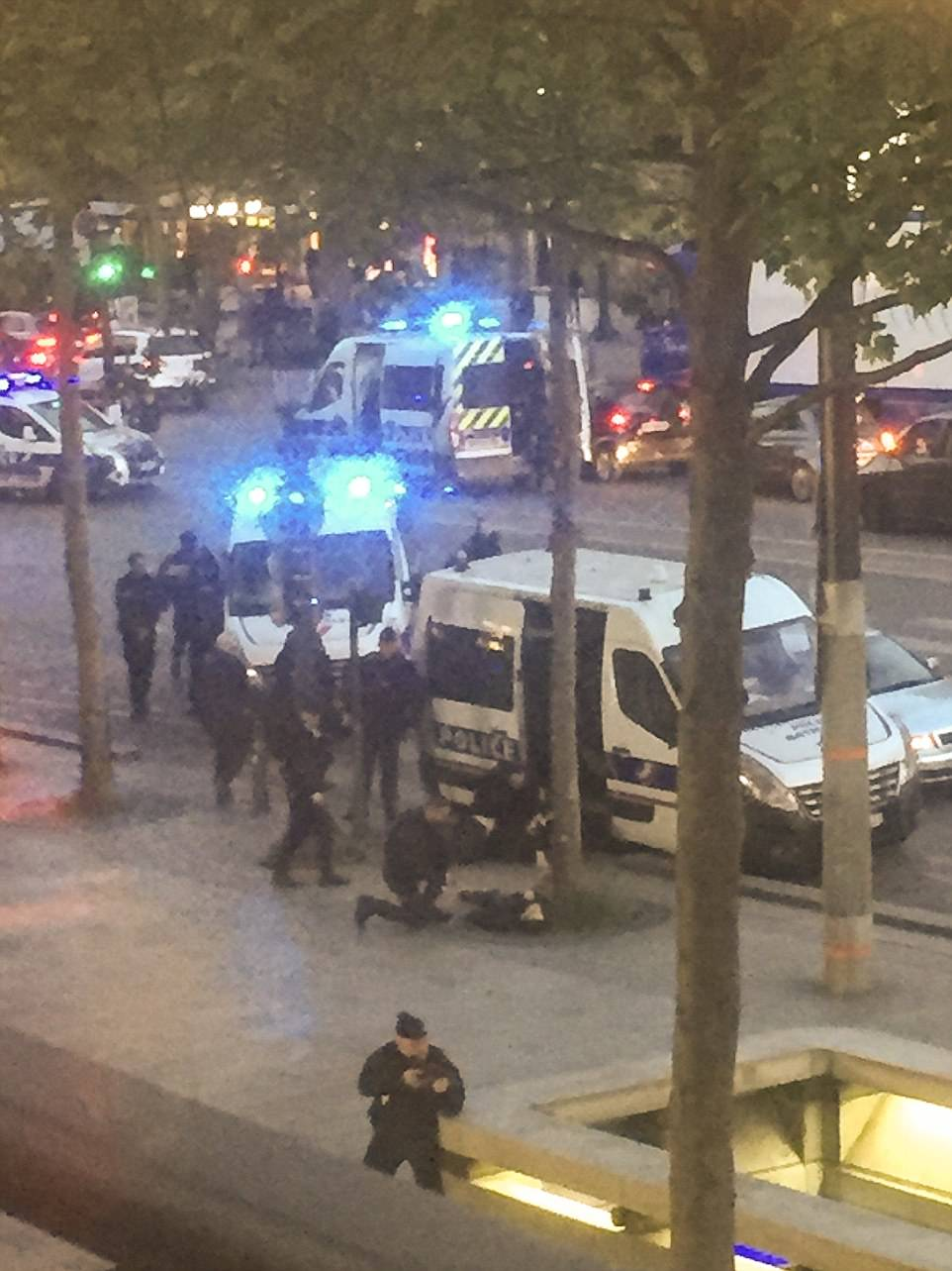 Pictured is armed police crowded two other officers, believed to have been shot in the attack, on Champs Elysees on Thursday night