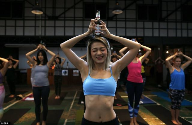 Astounding photos show nimble yogis deftly balancing a beer bottle on their heads as they practice 'beer yoga'in Bangkok, Thailand