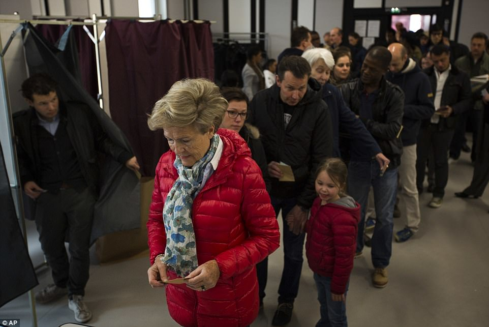 People line up before casting their vote for the first-round presidential election at a polling station in Paris, Sunday, April 23, 2017