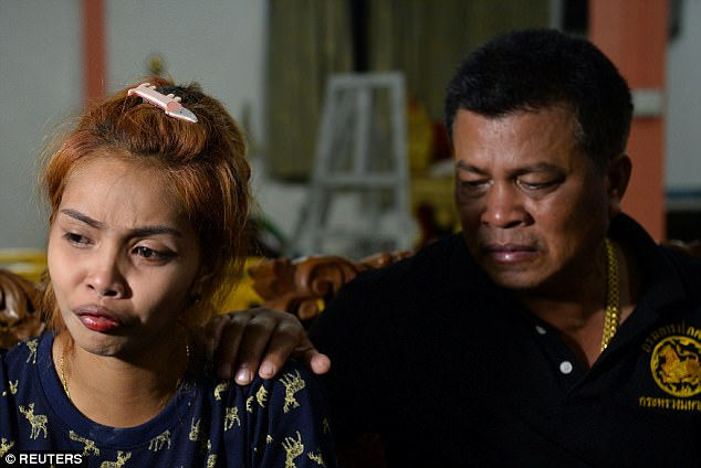 The 21-year-old is comforted by her father following an emotional service at a temple in Phuket