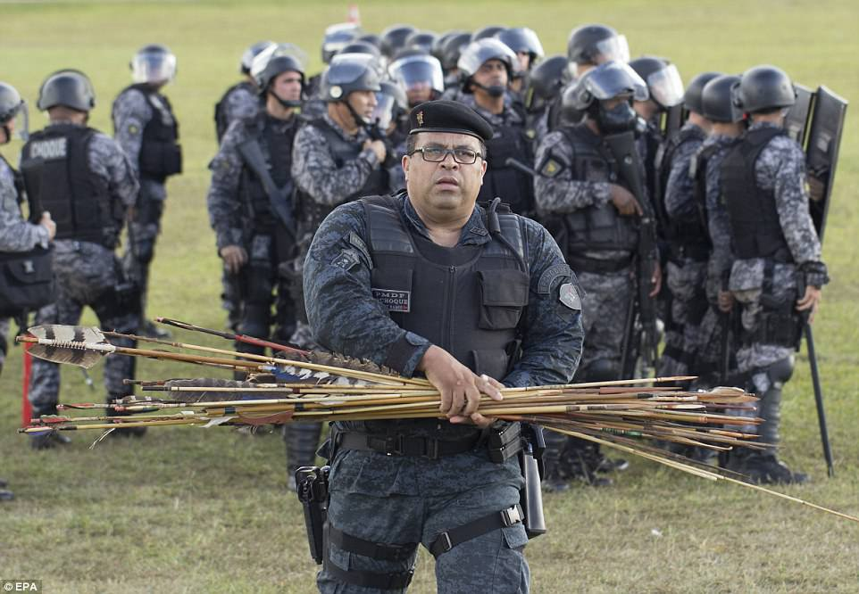 A member of the Brazilian police gathers arrows fired by Brazilian natives during the protest. According to police, no officers were hurt during the protest