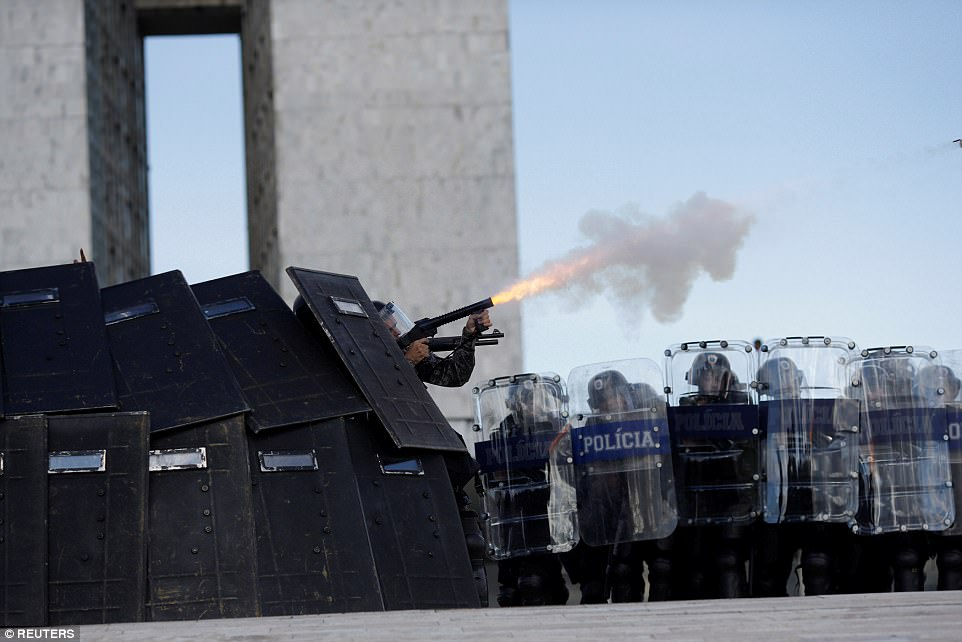 Police fire tear gas canisters at protesters as they huddle underneath huge shields while they face off with demonstrators