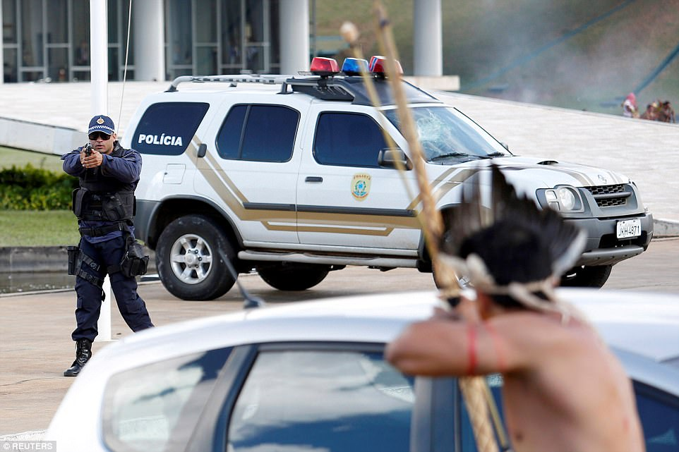A police officer stands in front of his 4x4 and aims his gun at a tribe member, who in turn, aims his bow and arrow back at him