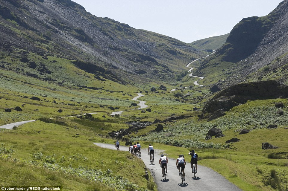 A long road ahead: Cyclists prepare to ascend Honister Pass at Lake District National Park in Cumbria with the breathtaking view of the ride in front of them