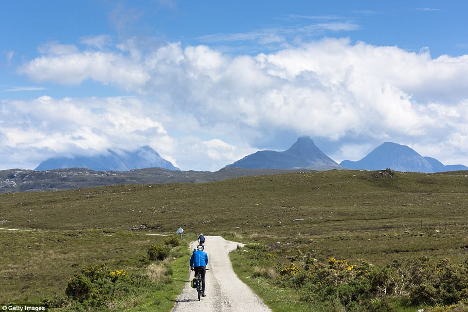 Cloud-covered mountains: Cyclists riding towards Stac Pollaidh in the glacier mountain range in the North West Highlands Geopark in the Coigach region of the Scottish Highlands