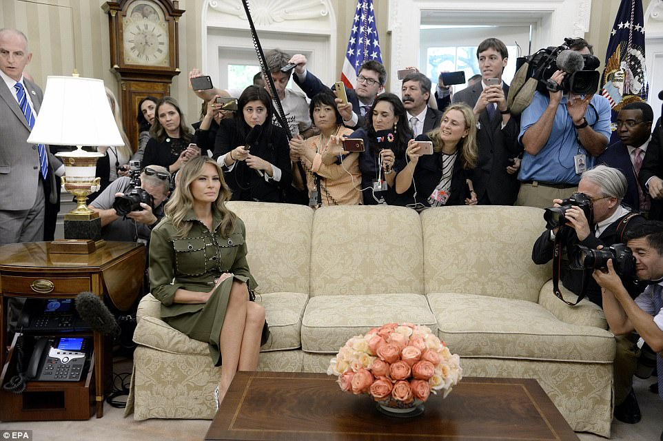 Melanie looked stoic while reporters crowded behind the couch that she was sitting on in the Oval Office