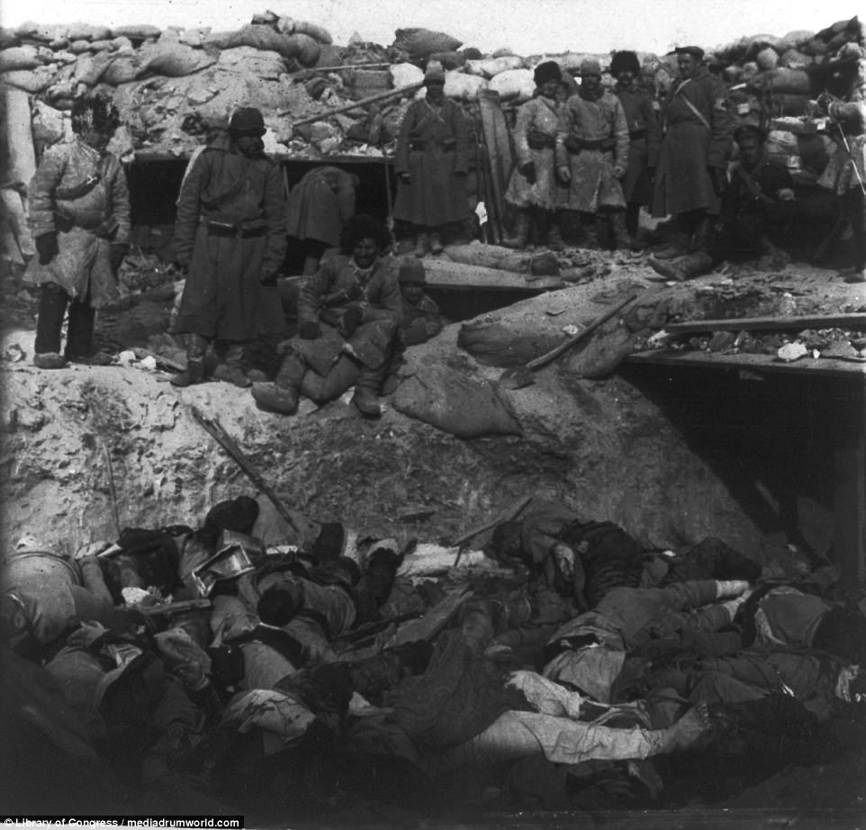 Tens of thousands of soldiers on each side of the conflict lost their lives. Russian soldiers are pictured looking into a trench filled with the bodies of Japanese soldiers in the disputed Port Arthur in Manchuria, which was the scene of a prolonged siege in a decisive clash in the Russo-Japanese war