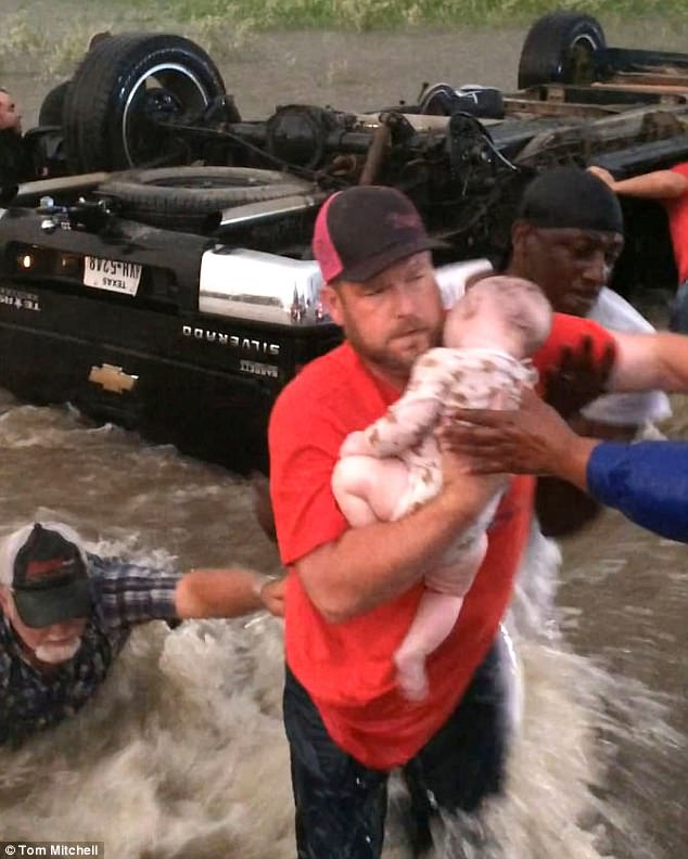 A dramatic video shows the moment a family and their dying baby were rescued from their flipped truck surrounded by rapidly rising floodwaters