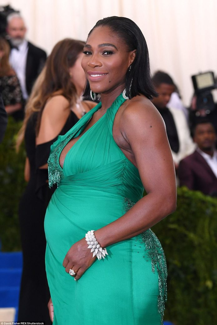 Green goddess: Serena Williams flashes her diamonds, and that bump, as she arrives in a Versace gown