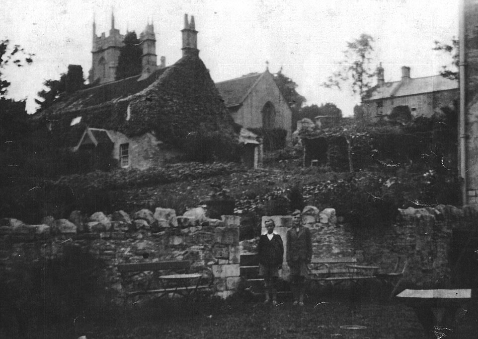 Two young boys are seen in the beer garden, with the village church in the background, at the turn of the century