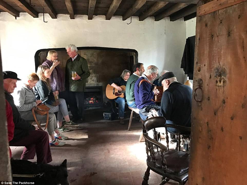 Customers gather around a makeshift fire and play music during one of their pop-up events to drum up support