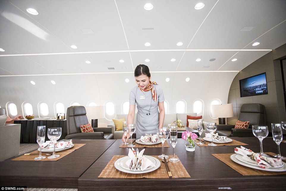 Fine dining: A cabin crew member lays a polished wood table with bespoke china for exceptional meal times