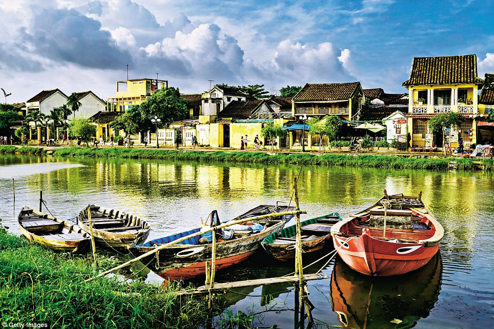 An idyllic riverside scene in Hoi An, with fishing boats moored on the gentle water