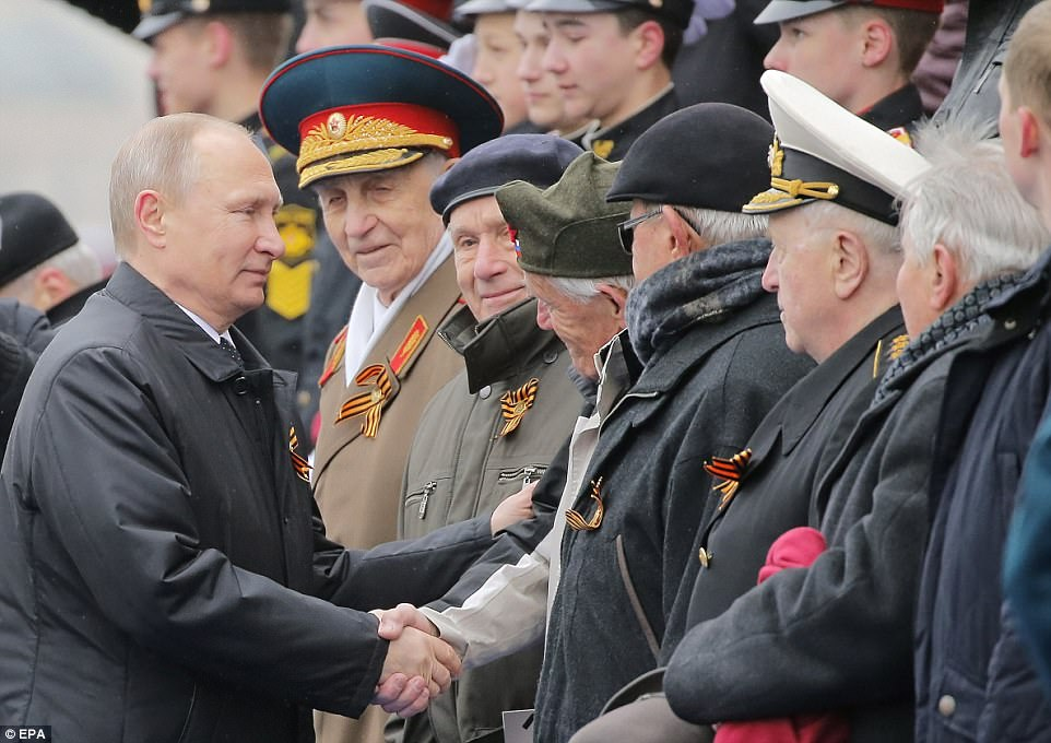 Russian president Vladimir Putin (pictured meeting World War Two veterans) personally took the salute at the parade. But a fly-past of 72 aircraft was cancelled