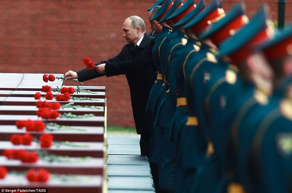 Vladimir Putin lays flowers at the Hero Cities memorial by the Kremlin Wall. He has warned his army can 'repel any aggression'