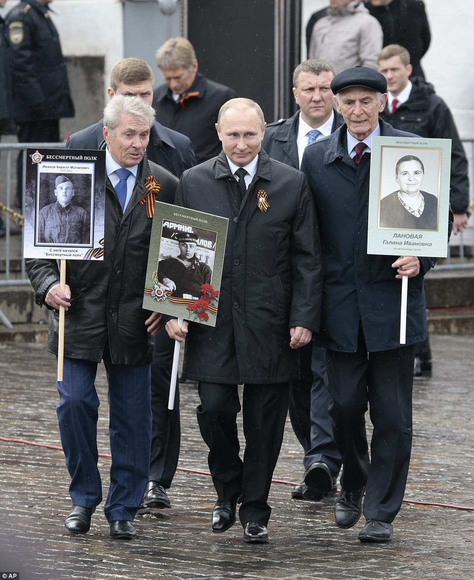 Russian President Vladimir Putin (centre) holds a photograph of his father in a naval uniform, as he joins people carrying portraits of relatives who fought in the Second World War
