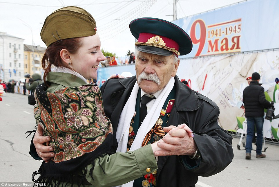 A pensioner in Ryazan, south east of Moscow, shares a dance with a young women as they celebrate Victory Day