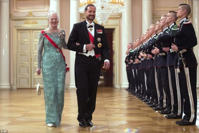 Crown Prince Haakon of Norway leads Queen Margrethe of Denmark wearing a floor length turquoise dress