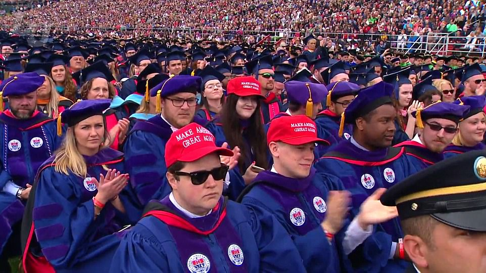 Three Liberty graduates are seen wearing Trump's presidential slogan: 'Make America Great Again'